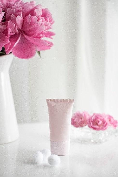 Photo montrant un packaging de produit cosmétique rose pâle à côté d'un bouquet de fleur