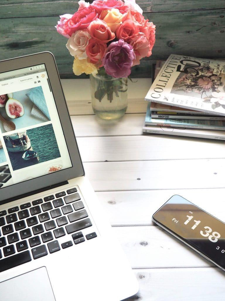Ordinateur posé sur une table avec un bouquet de fleurs et des magazines