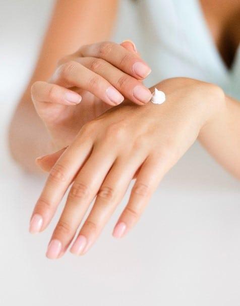 Femme prenant soin de ses mains en leur appliquant de la crème